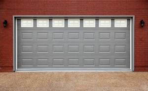 Big garage with gray doors, brick wall and asphalt driveway